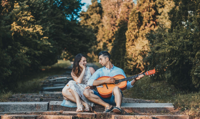 man-and-woman-sitting-on-steps-with-man-playing-acoustic-guitar