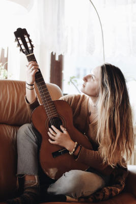 woman-playing-classical-guitar-on-couch