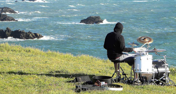 A lone drummer playing alongside a cliff overlooking the ocean