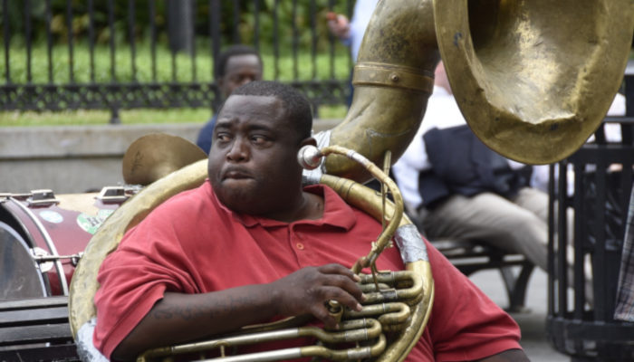 man-playing-tuba-on-a-park-bench