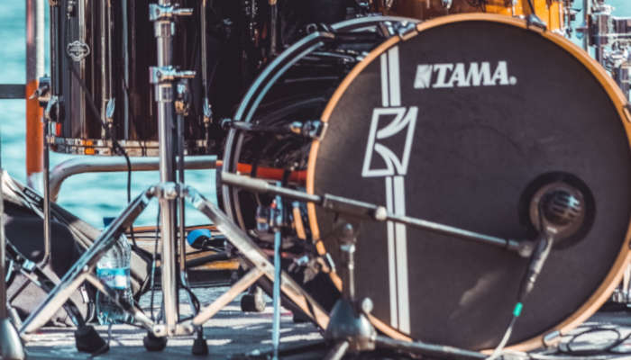 Closeup of a black bass drum in front of a drum set