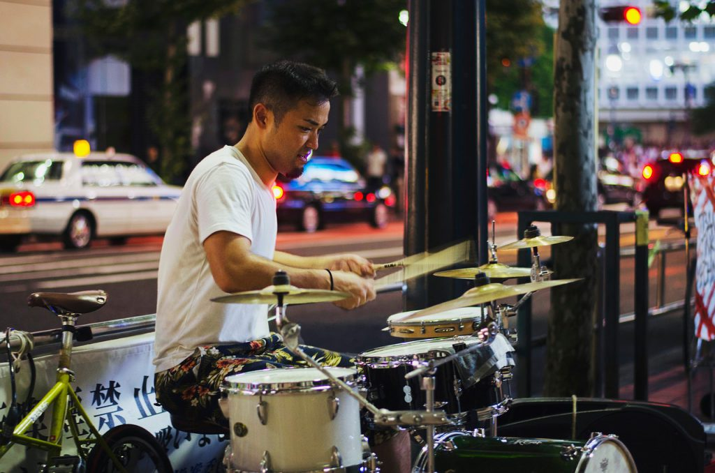 Man playing drums on Hong Kong sidewalk