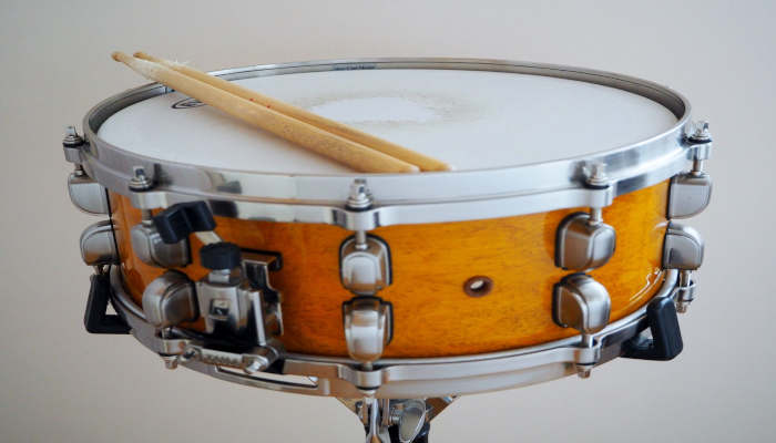Closeup of a yellow snare drum with drum sticks