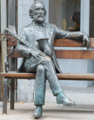 Metal statue of Adolphe Sax seated on a wooden bench with saxophone in hand
