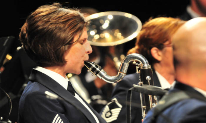Female United States Navy officer playing bass clarinet in concert