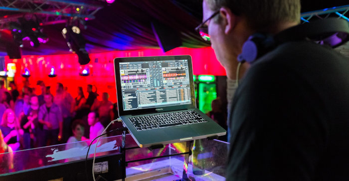 DJ playing music on a laptop in front of audience