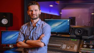 Man standing in music recording studio with arms crossed