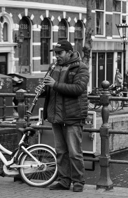 Black and white photo of a man playing a clarinet while standing on a small bridge
