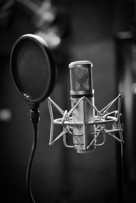 Black and white photo of studio microphone with black pop filter