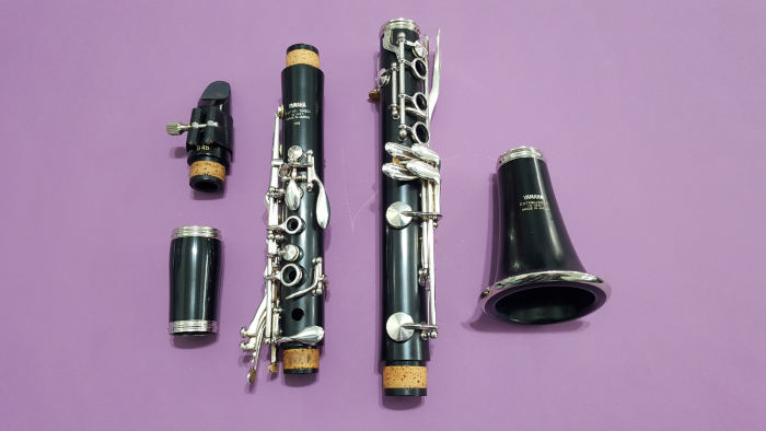 Disassembled clarinet on violet background
