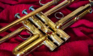 Shiny gold trumpet laying on a red towel