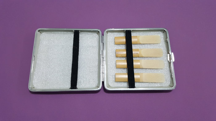 Clarinet reed case with reeds on a violet background