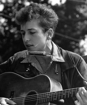 Black and white photo of Bob Dylan playing harmonica and acoustic guitar