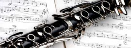 A clarinet resting on top an open book of sheet music