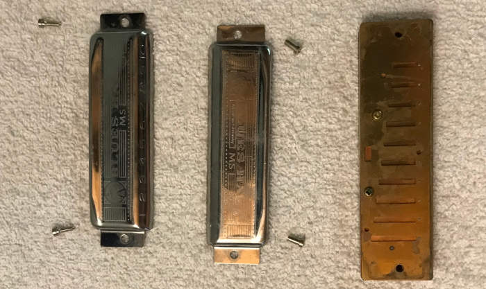 A disassembled Blues Harp harmonica on a white towel