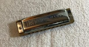 A Blues Harp harmonica sitting atop a white towel
