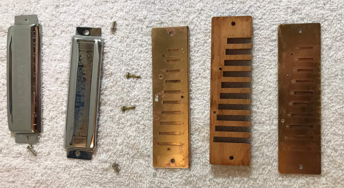 A disassembled Blue Harp harmonica with parts laid across a white towel