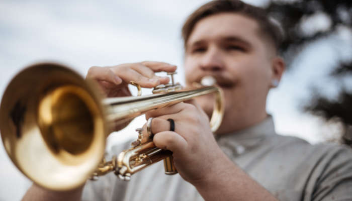 Man in grey shirt blowing into trumpet with focus on hands