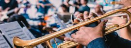 Black man in a blue shirt playing trumpet in an orchestra band