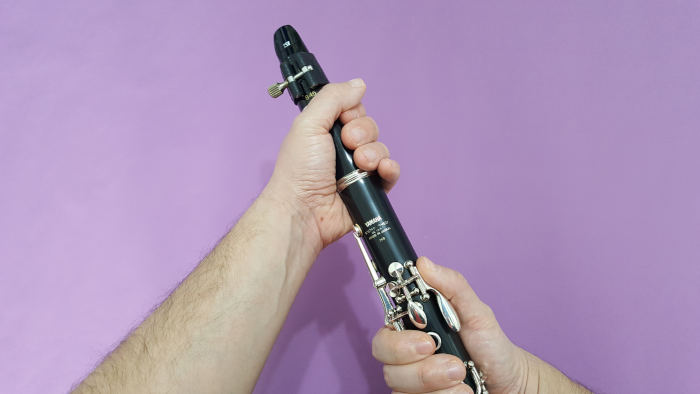 A man twisting a clarinet barrel onto an upper joint on a purple background