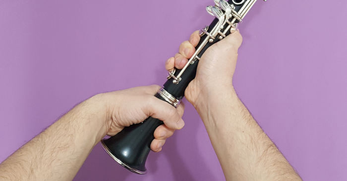 A man twisting a clarinet bell onto a lower joint on a purple background