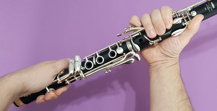 A man twisting the upper and lower joints of a clarinet on a purple background