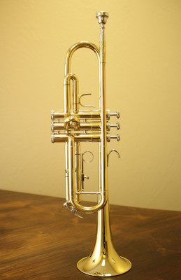 A b-flat trumpet sitting horn-down on a wood table
