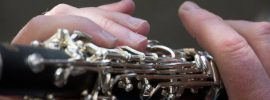 A pair of hands holding a clarinet to show proper fingerings