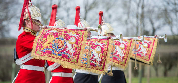 Ceremonial troops playing fanfare trumpets with royal coat of arms banners