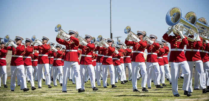 A military brass band dressed in red uniforms playing on an athletic field