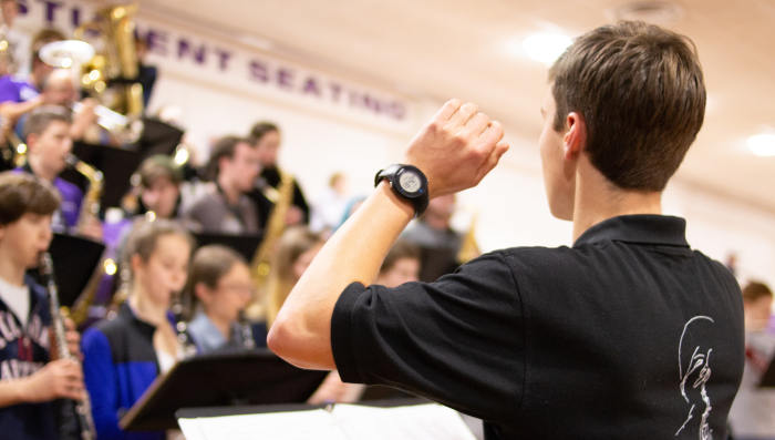 A male band director conducting a high school band