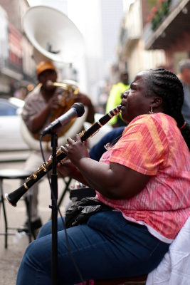 Black woman playing clarinet seated beside a standing microphone