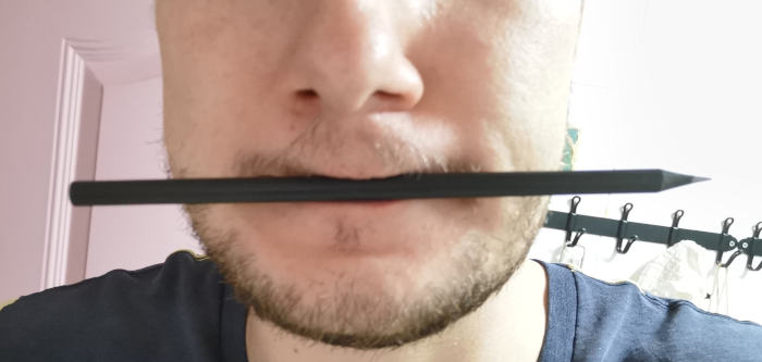 Man holding black pencil between lips