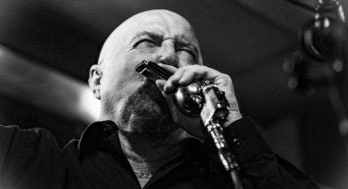 Black and white photo of a bald man in a black shirt playing blues harmonica on stage