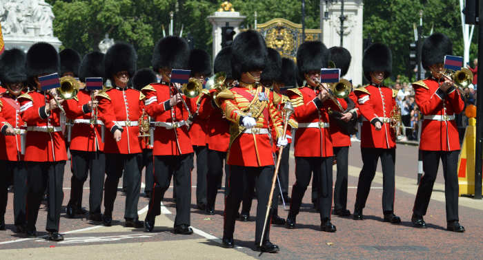 Marching band parading down a London street wearing a traditional royal guard uniform