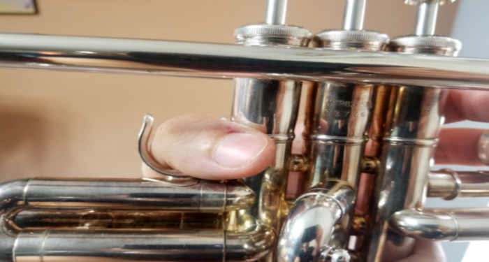 A silver-colored trumpet being held in a man's left hand with thumb inserted into first valve ring