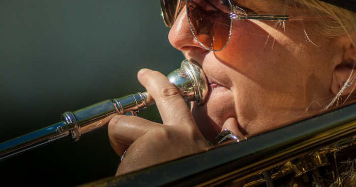 A woman playing trombone outdoors while wearing sunglasses