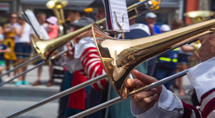 A line of brass musicians performing in an urban street with two trombonists in the foreground