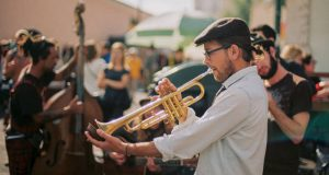 Man wearing white shirt, brown derby and glasses playing trumpet outside with orchestra while