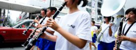 Rows of Asian kids playing various woodwind and brass instruments in a parade in the street