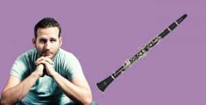 Man looking contemplative beside an Etude student clarinet model ECL-100 on purple background