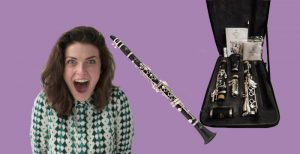 Woman looking excited next to Buffet Prodige clarinet with case and accessories on purple background
