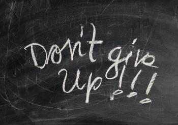"""Don't give up"" written in white chalk on a blackboard"