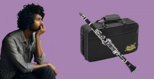 Dark-skinned man staring distantly at a Jean Paul USA CL-300 student clarinet with case on purple background
