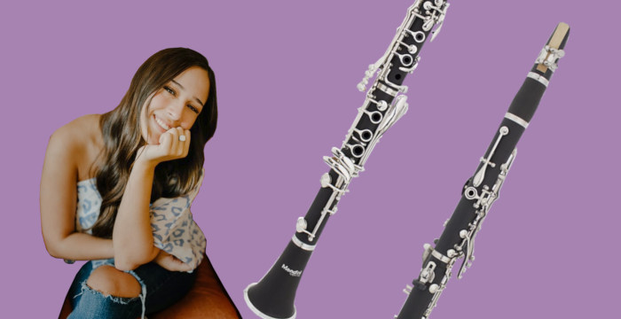 Brown-haired woman sitting in a brown leather chair beside two clarinets on purple background