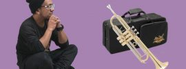 Asian man in dark clothing sitting cross legged looking at a Jean Paul USA TR-330 standard trumpet on a purple background