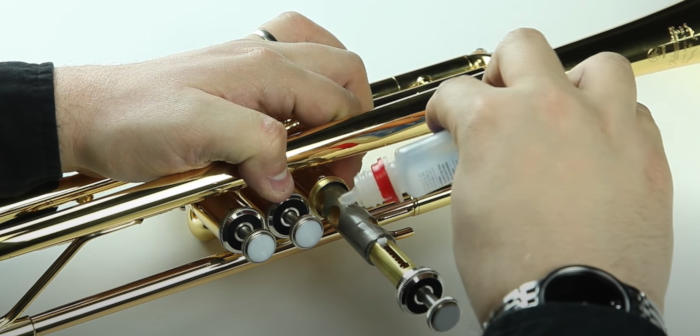 A man holding a trumpet with one hand and oiling the first valve with the other on a white background