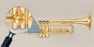Trumpet with a magnifying glass focused on the second valve slide on grey background