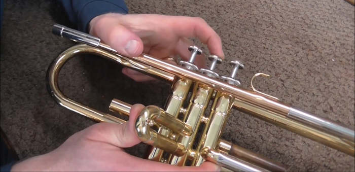 A pair of hands holding a trumpet and pressing on a valve slide