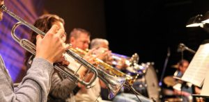 A line of men playing trumpet in an orchestra